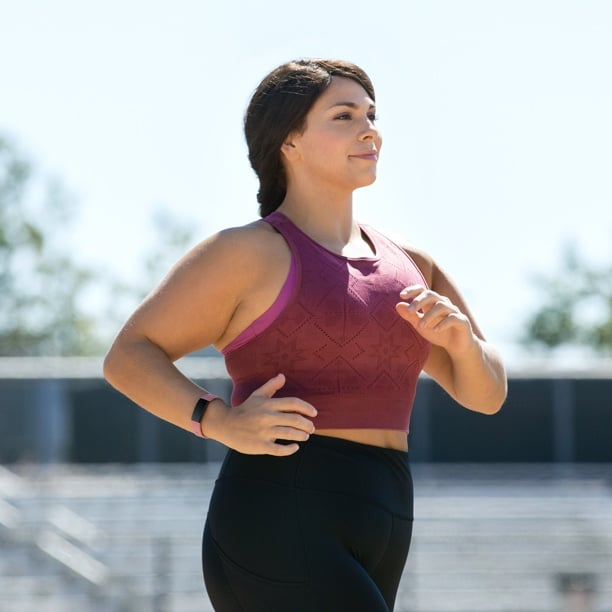 Woman running with her Fitbit