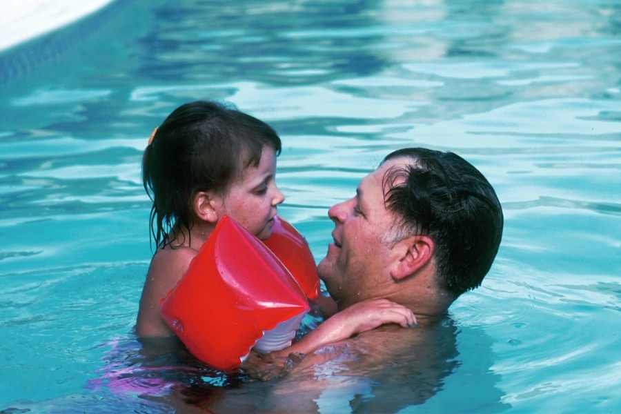 Father and daughter playing in the pool